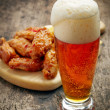 Glass of fresh beer and fried chicken wings — Stock Photo #50622031