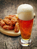 Glass of fresh beer and fried chicken wings — Stock Photo