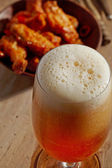 Glass of fresh beer and fried chicken wings — Foto de Stock