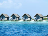 Water bungalows with steps beside sea — Stock Photo