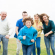 Happy family running on a green meadow — Stock Photo