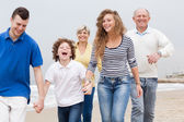 Happy family walking on the beach — Stock Photo