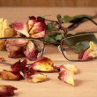 Glasses and dry rose with petals close up — Stock Photo