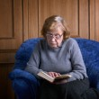 The grandmother in an armchair with the book — Stock Photo #12188705