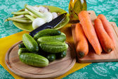 Green cucumbers with onions garlic and carrots on a kitchen tabl — Stock Photo