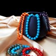 Bracelets and beads on a golden fabric — Stock Photo