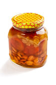 Bank of honey with the candied fruit and nuts on a white backgro — Stock Photo