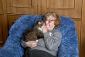 The grandmother with a cat in house conditions — Stock Photo