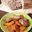 Dish with meat and carrots the cut bread on a kitchen table — Zdjęcie stockowe