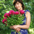 Stock Photo: Womof average years with flowers in garden