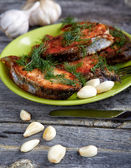 Plate with fried fish and garlic on a wooden table — Stock Photo
