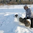 Woman plays with a dog in the winter afternoon — Stock Photo #35879407