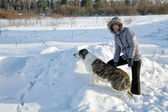 Woman plays with a dog in the winter afternoon — Stock Photo