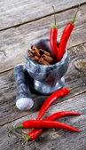 Argamassa com canela e pimenta pimenta em uma velha mesa — Fotografia Stock