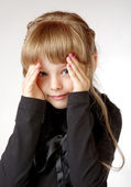 Little girl in a black dress shuts face with the hands — Stock Photo