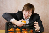 The young man joyfully eats tangerines from a box — Stock Photo