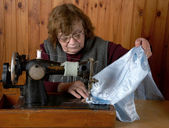 The old woman sews — Stock Photo