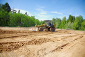 The grader clears away a ground In the afternoon — Stock Photo