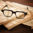 Old writing-books and glasses on a wooden table — Stock Photo #43386283