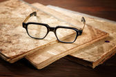 Old writing-books and glasses on a wooden table — Stock Photo