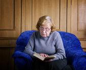 La vecchia siede in poltrona e legge il libro — Foto Stock