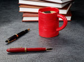 Pens with a cup of coffee and organizers — Stock Photo