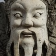 Wat Pho stone guardian face close up, Thailand - Stock Photo
