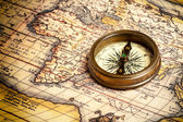 Old vintage compass on ancient map — Stock Photo
