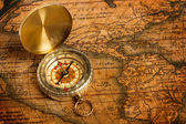 Old vintage golden compass on ancient map — Stock Photo