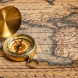 Old vintage golden compass on ancient map - Stock Photo