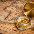 Stock Photo: Old vintage golden compass on ancient map