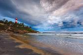 Gathering storm on beach and lighthouse on sunset. Kerala, India — Stock Photo
