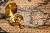 Old vintage golden compass on ancient map — Stok fotoğraf