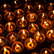 Burning candles in Tibetan Buddhist temple - Stock Photo