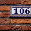 Decorated house number on brick wall in Europe. Bruges (Brugge), - Stock Photo