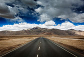 Road on plains in Himalayas with mountains — Stock Photo