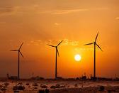 Gerador sihouettes de turbinas do vento sobre o sol — Fotografia Stock