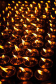 Burning candles in Tibetan Buddhist temple — Stock Photo