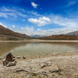 Trekking hiking boots at mountain lake in Himalayas — Stockfoto