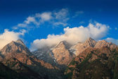 Himalayas summits in clouds on sunset — Stock Photo
