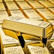 Gold bar on stacks of gold bullions close up — Stock Photo