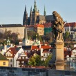 Statue on Charles Brigde against St. Vitus Cathedral in Prague — Stock Photo