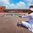 Muslim man feeding pigeons in India largest mosque Jama Masjid — Stock Photo