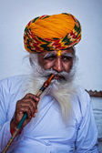 Old Indian man smokes hookah (waterpipe) in Mehrangarh fort — Stock Photo