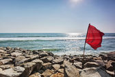 Red flag on rocky beach — Stock Photo