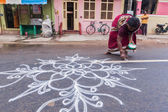 Unidentified India woman drawing Kolam — Stock Photo