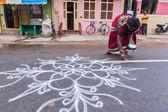 Unidentified India woman drawing Kolam — Stock Photo
