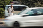 Unidentified Indian man crossing the street with moving cars — Stock Photo