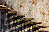 Stairs casting shadow on old weathered wall — 图库照片