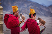 Two Tibetan Buddhist monks blowing conches during morning pooja — Stock Photo